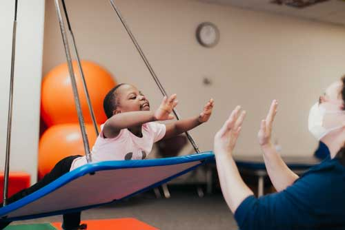 Child swinging on platform working with physical therapist